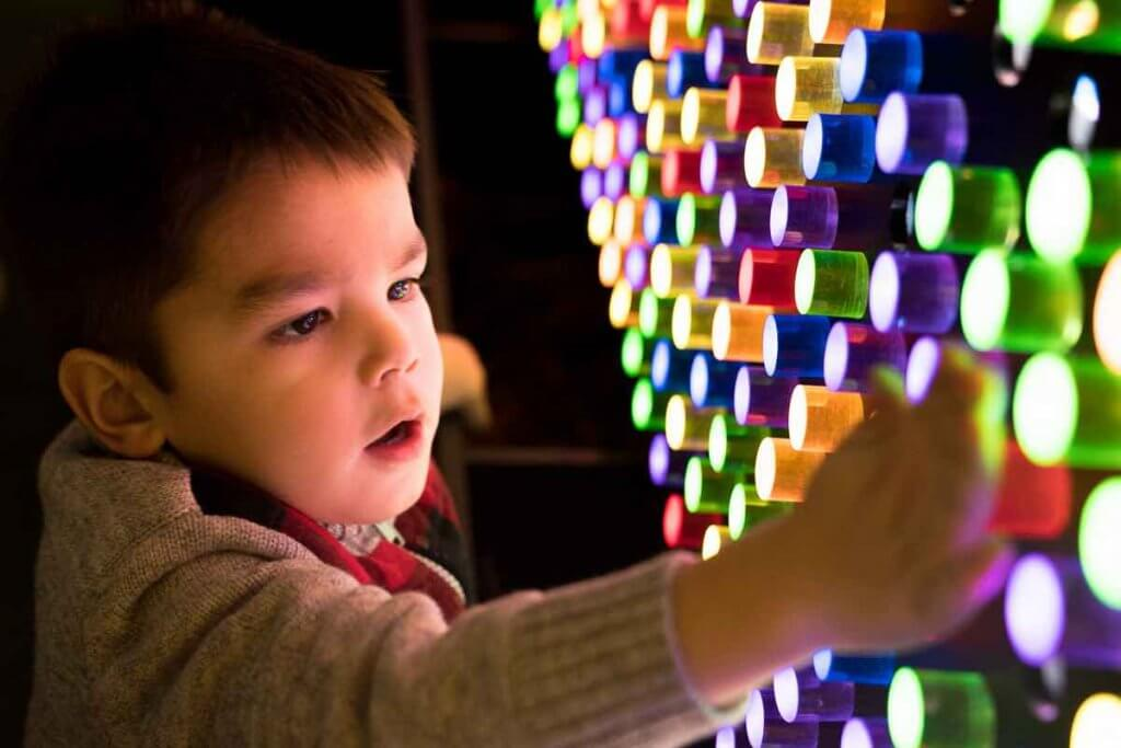Lumaze Indoor Light Festival in Seattle review featured by top Seattle blogger, Marcie in Mommyland: A boy plays with lighted pegs in a pegboard at Lumaze Seattle