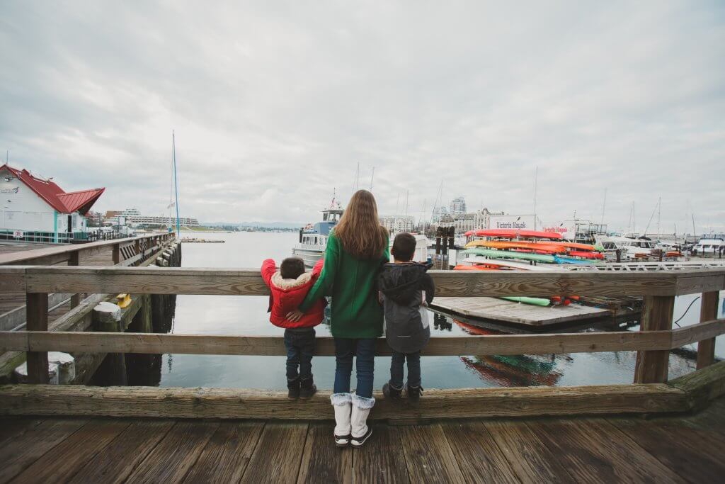 Best Winter Weekend Getaways from Seattle featured by top Seattle travel blogger, Marcie in Mommyland: Image of a woman and two boys looking out at Victoria Harbour in Victoria BC in winter