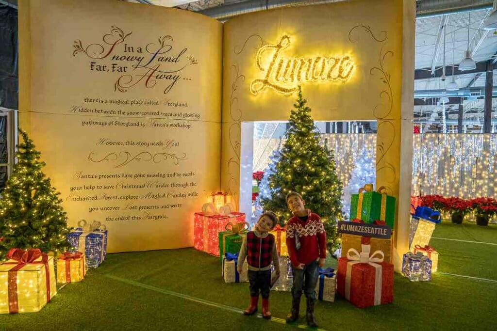 Lumaze Indoor Light Festival in Seattle review featured by top Seattle blogger, Marcie in Mommyland: Entrance to the Lumaze Seattle Garden Walk featuring an oversized book, a Christmas tree, and presents