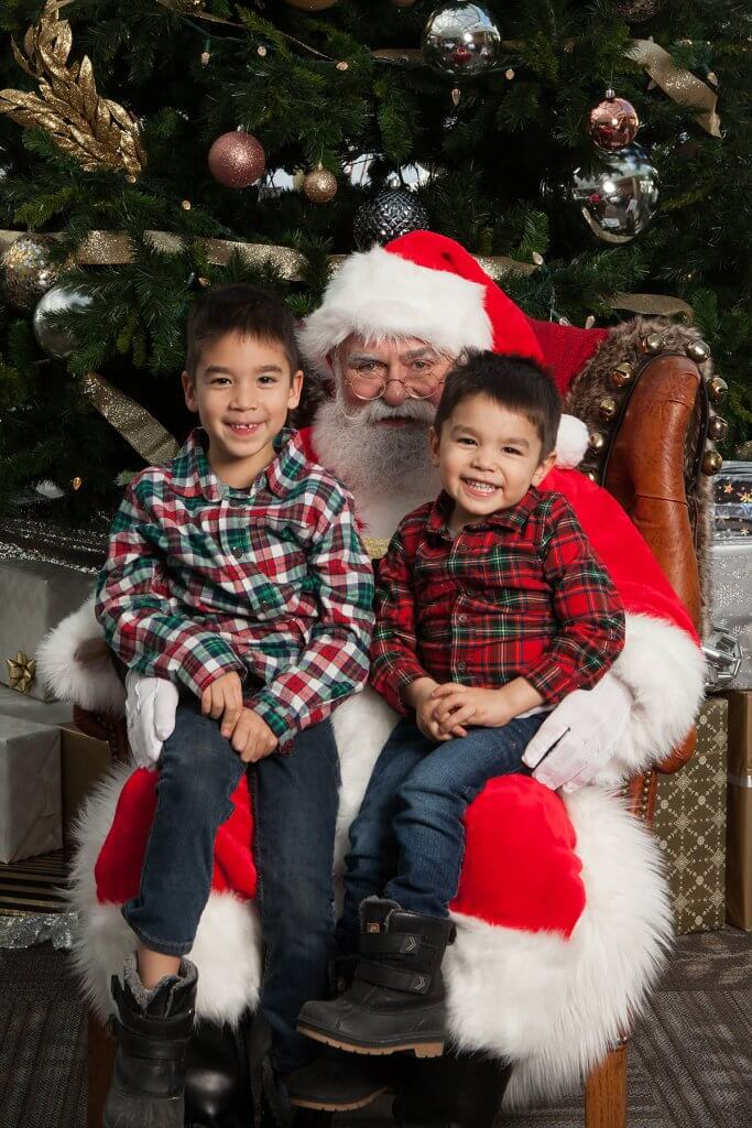 Christmas in Victoria BC: the Best Kid Friendly Festivities featured by top US family travel blogger, Marcie in Mommyland: Two boys wearing Christmas plaid shirts sitting on Santa's lap for a photo at the Santa Brunch in Victoria, BC