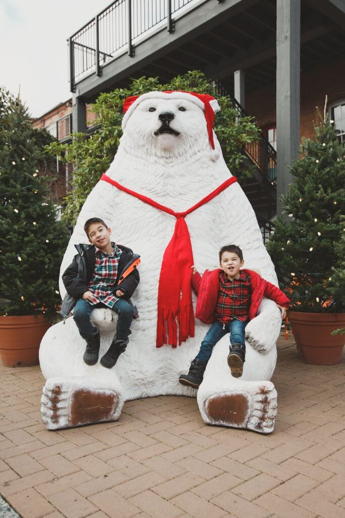 Christmas in Victoria BC: the Best Kid Friendly Festivities featured by top US family travel blogger, Marcie in Mommyland: Kids sitting in a giant polar bear statue in Victoria, BC