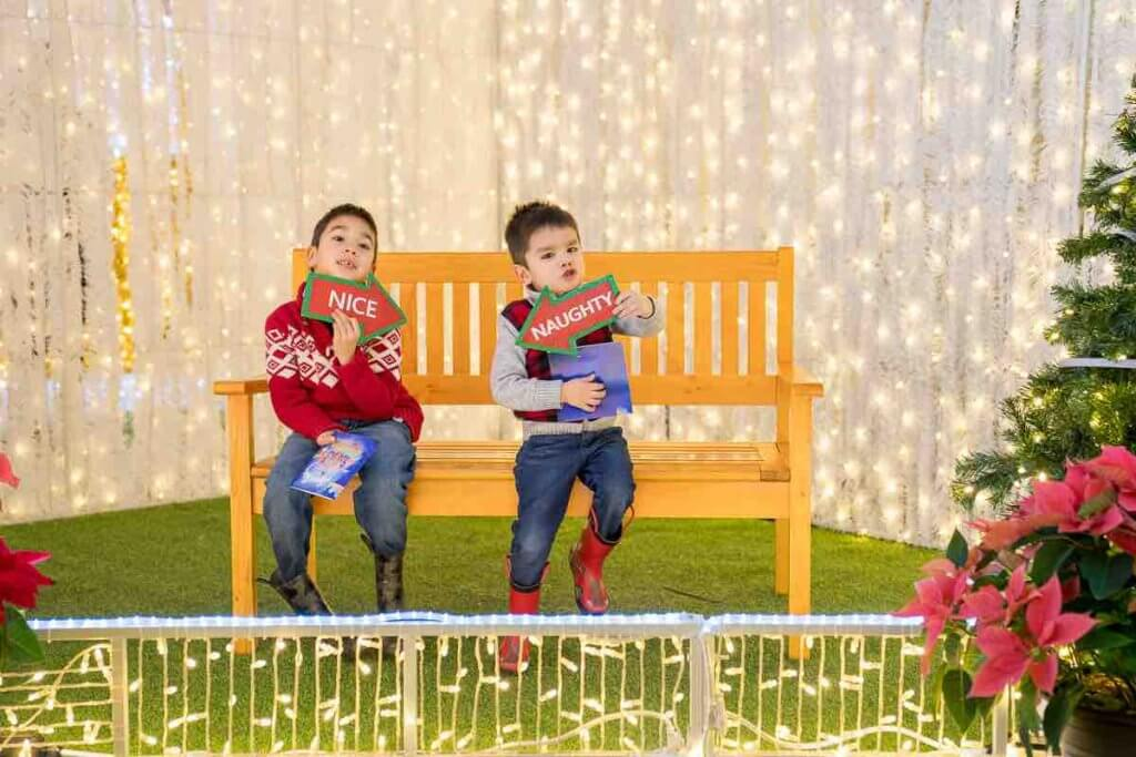 Lumaze Indoor Light Festival in Seattle review featured by top Seattle blogger, Marcie in Mommyland: Little boys sit on a bench holding signs that say naughty and nice at a photo op at Lumaze Seattle