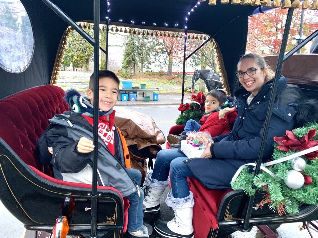 Christmas in Victoria BC: the Best Kid Friendly Festivities featured by top US family travel blogger, Marcie in Mommyland: Mom and two boys sitting inside a luxurious carriage ready to explore Victoria, BC