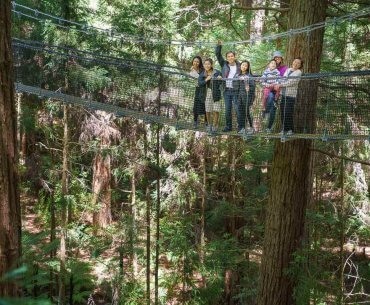 Redwoods Tree Walk in Rotorua, New Zealand travel guide featured by top family travel blogger, Marcie in Mommyland: Group of people posing on the Rotorua Tree Walk