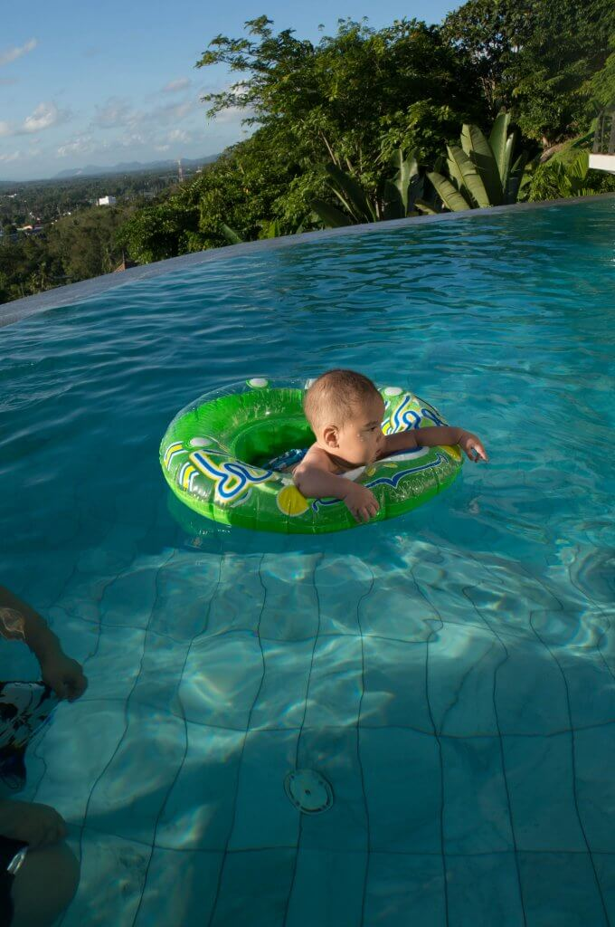 Where to Stay in Phuket with Kids, travel tips featured by top family travel blogger, Marcie in Mommyland: Baby swimming in an infinity pool at a Phuket villa in Thailand
