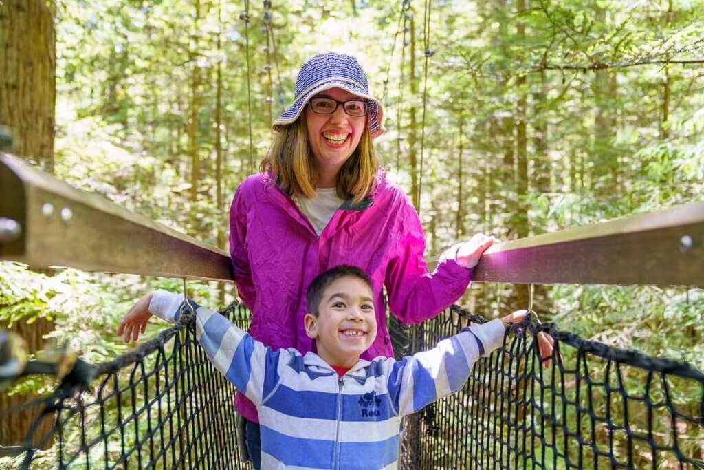 Redwoods Tree Walk in Rotorua, New Zealand travel guide featured by top family travel blogger, Marcie in Mommyland: Mom and son walking across a suspension bridge in Rotorua, New Zealand