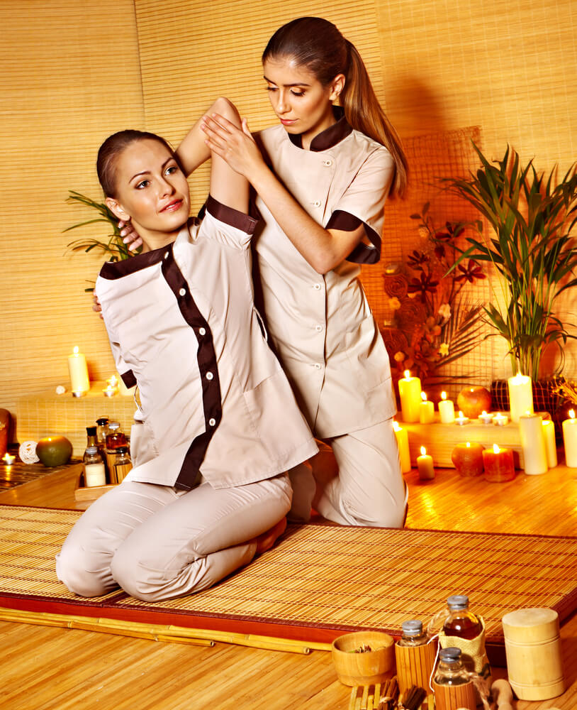 Where to Stay in Phuket with Kids, travel tips featured by top family travel blogger, Marcie in Mommyland: Young woman getting massage in bamboo spa..