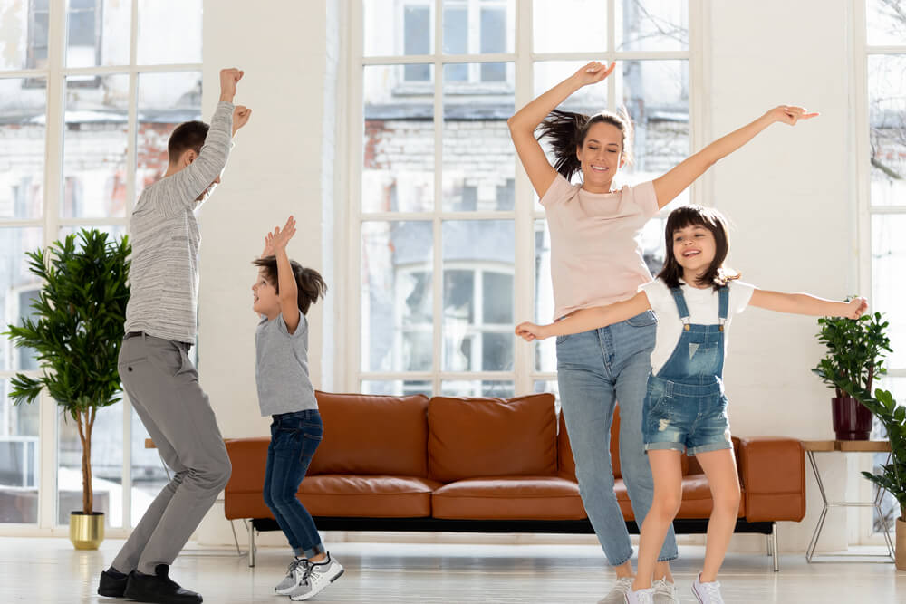The Ultimate List of Indoor Games, Activities and Workouts to Keep Your Kids Active featured by top Seattle lifestyle blogger, Marcie in Mommyland: Joyful young mommy jumping with adorable daughter, happy father dancing with cute son to favorite energetic music tracks in living room at home. Joyful family enjoying dancing party in living room.