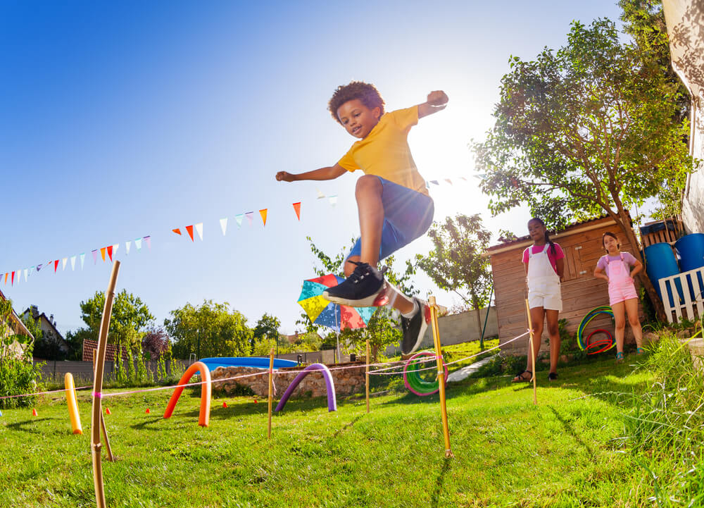 The Ultimate List of Indoor Games, Activities and Workouts to Keep Your Kids Active featured by top Seattle lifestyle blogger, Marcie in Mommyland: Cute black curly hair boy jump over strings passing course of obstacles playing competitive game with friends