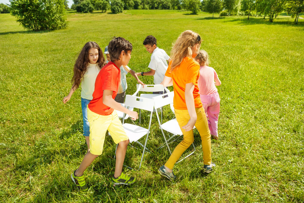 The Ultimate List of Indoor Games, Activities and Workouts to Keep Your Kids Active featured by top Seattle lifestyle blogger, Marcie in Mommyland: Kids run around chairs playing a game outside in summer period