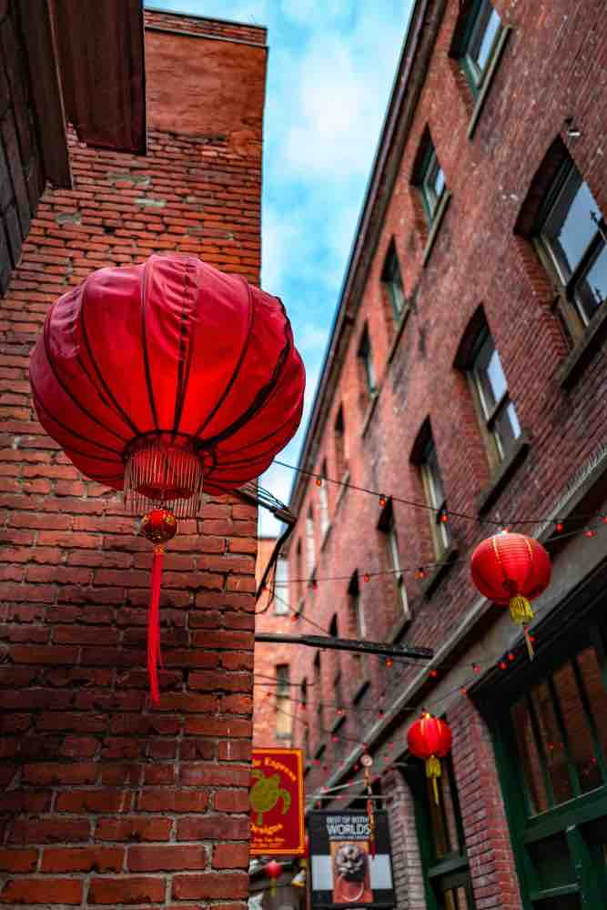 Victoria with Kids: 13 Kids Activities to Do when Visiting Victoria Canada featured by top family travel blogger, Marcie in Mommyland: A vertical low angle shot of Chinese lanterns in Fan Tan Alley, Chinatown, Victoria, BC Canada