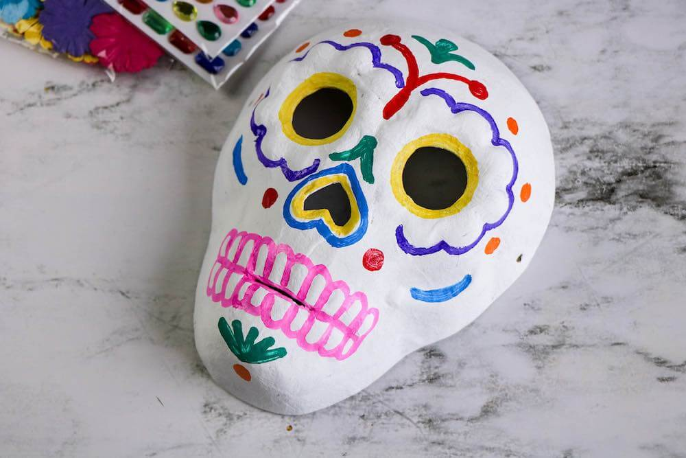 Dia de los Muertos Project for Kids: Sugar Skull Craft featured by top Seattle lifestyle blogger, Marcie in Mommyland: Use the paint pens to decorate your Day of the Dead craft