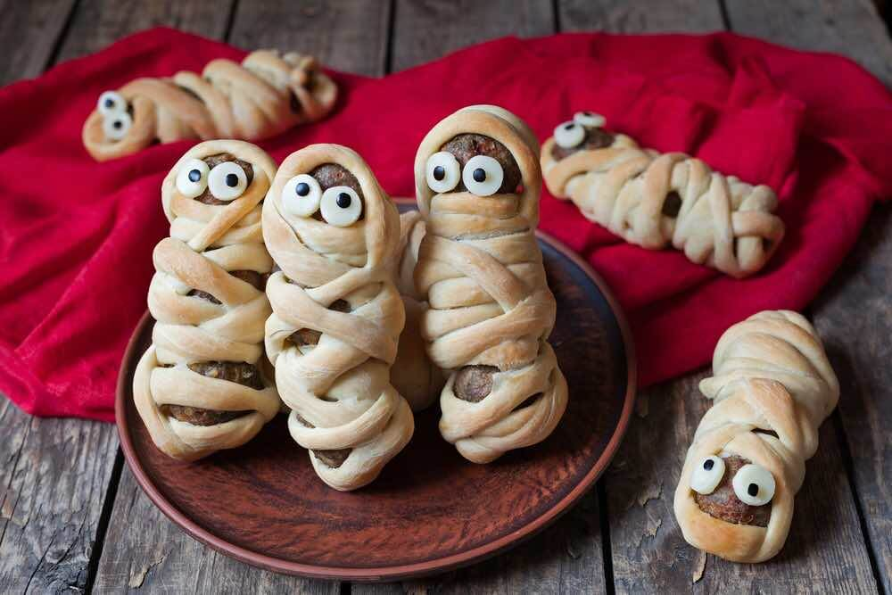 Fun Things to Do at Home on Halloween with Kids featured by top Seattle lifestyle blogger, Marcie in Mommyland. Scary halloween food meatball sausage mummies wrapped in dough with eyes on vintage wooden background. Halloween party decoration. Rustic style and natural light