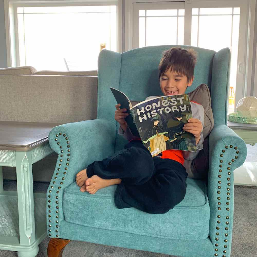 Honest History Magazine review featured by top Seattle lifestyle blogger, Marcie in Mommyland: Image of a boy reading Honest History magazine