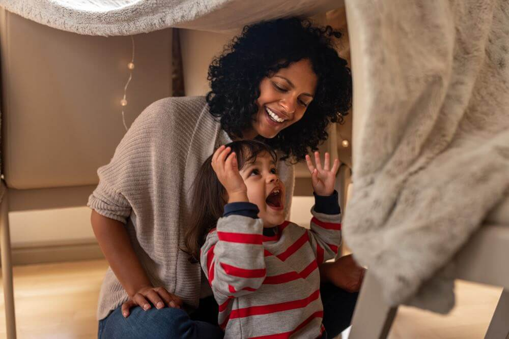 Fun Things to Do at Home on Halloween with Kids featured by top Seattle lifestyle blogger, Marcie in Mommyland. One of the easiest Halloween activities for kids is making a blanket fort. Image of a mother and child playing in a blanket fort