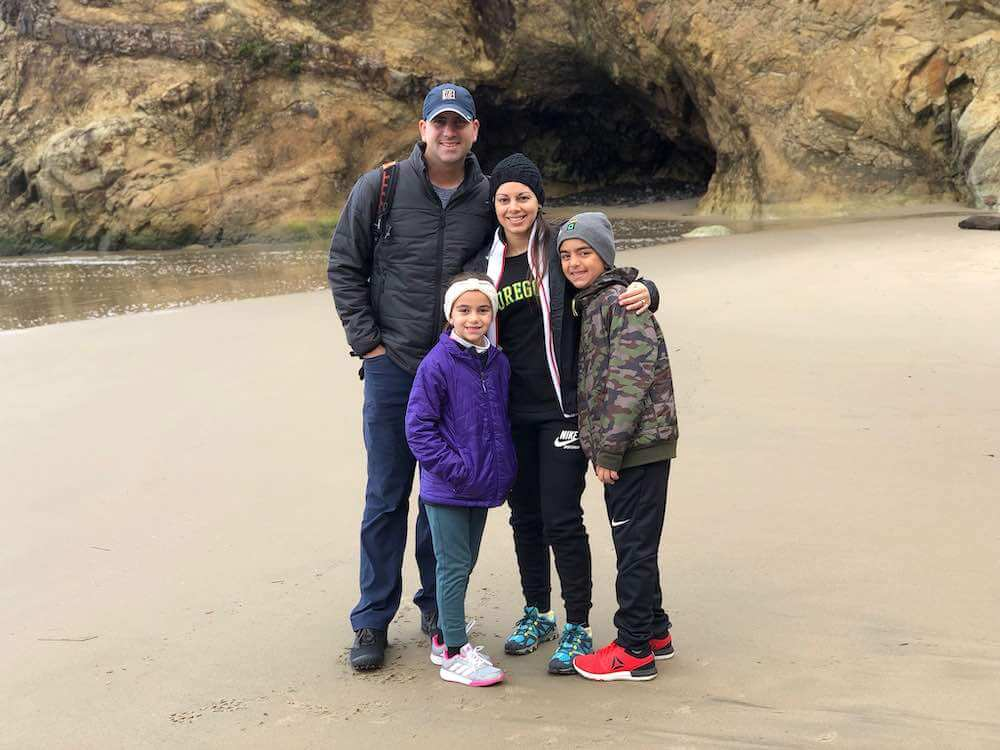 Best Winter Weekend Getaways from Seattle featured by top Seattle travel blogger, Marcie in Mommyland: Image of a family posing at Arch Cape Oregon in winter