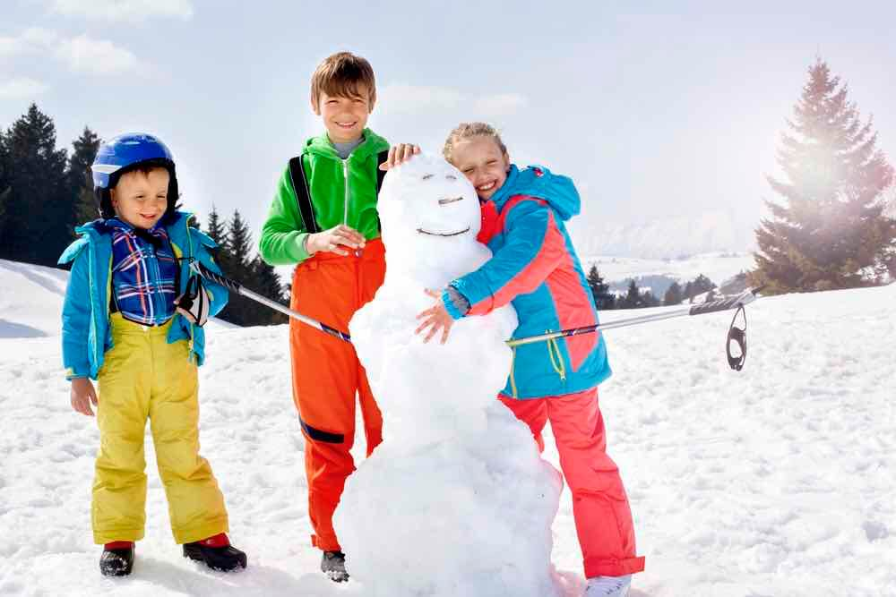 15 Free Festive Christmas Traditions That Don't Cost a Dime featured by top Seattle lifestyle blogger, Marcie in Mommyland: Building a snowman is the ultimate Christmas tradition with kids. Image of brothers and sister building a snowman