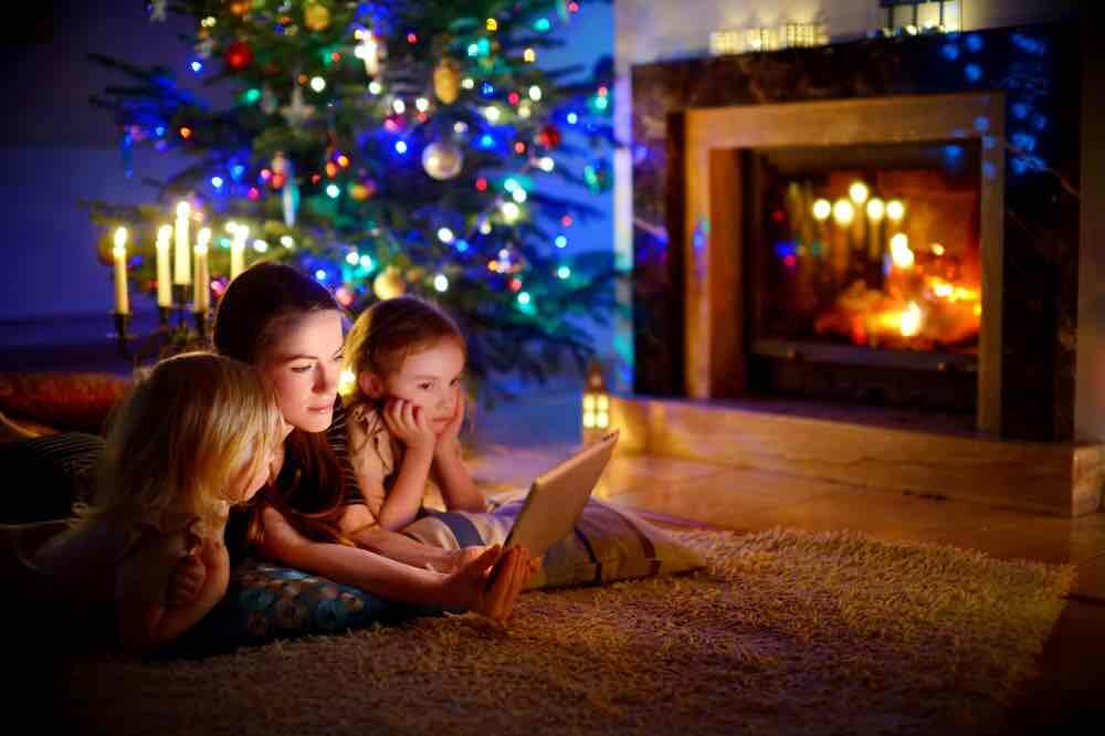 15 Free Festive Christmas Traditions That Don't Cost a Dime featured by top Seattle lifestyle blogger, Marcie in Mommyland: Try throwing a family sleepover in the living room on Christmas. Image of Young mother and her daughters using a tablet pc by a fireplace on warm Christmas evening