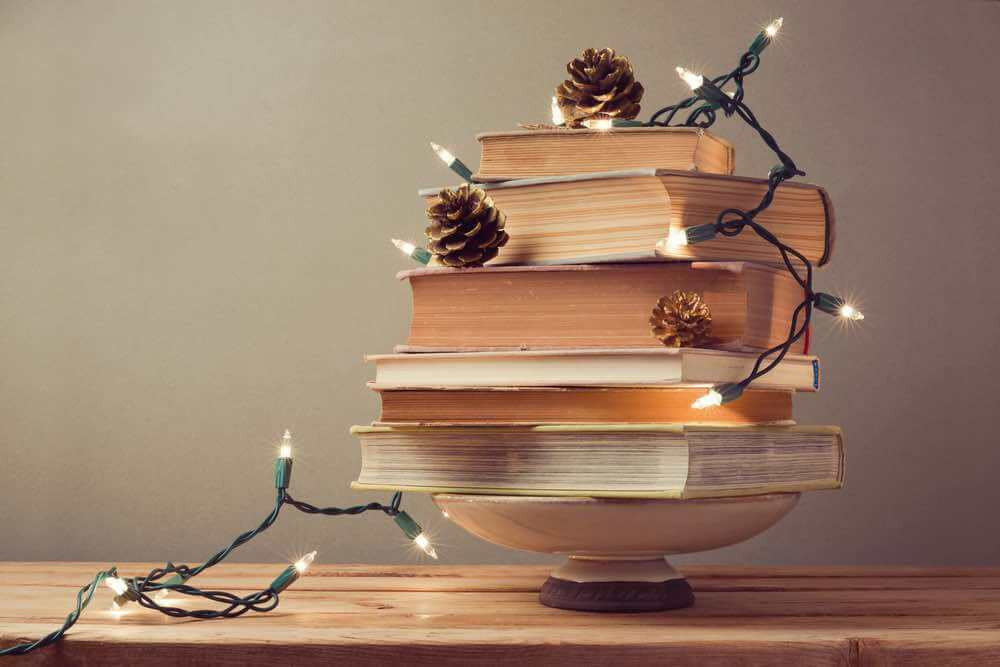 15 Free Festive Christmas Traditions That Don't Cost a Dime featured by top Seattle lifestyle blogger, Marcie in Mommyland: Create your own Christmas tree out of objects around your house. Image of Christmas tree made from books.