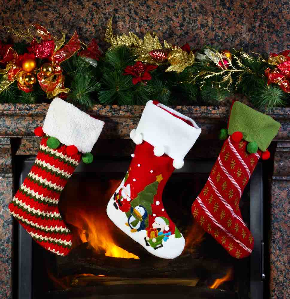 15 Free Festive Christmas Traditions That Don't Cost a Dime featured by top Seattle lifestyle blogger, Marcie in Mommyland: Learn about Christmas traditions from around the world. Image of Christmas stocking on fireplace background