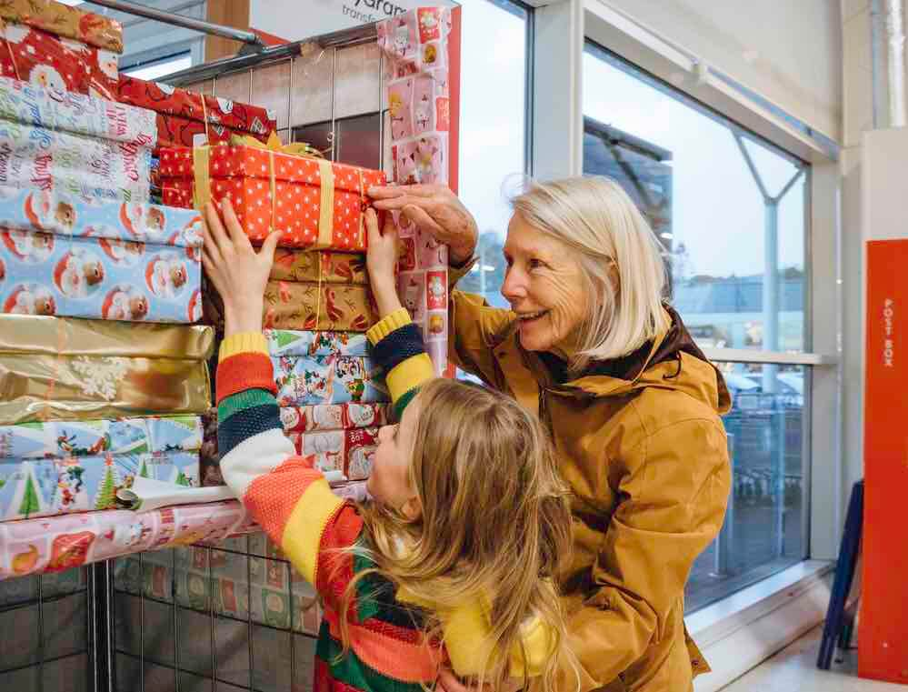 15 Free Festive Christmas Traditions That Don't Cost a Dime featured by top Seattle lifestyle blogger, Marcie in Mommyland: Volunteering is a great family Christmas tradition. Image of Little girl and her grandmother are donating a Christmas charity box in their local supermarket.