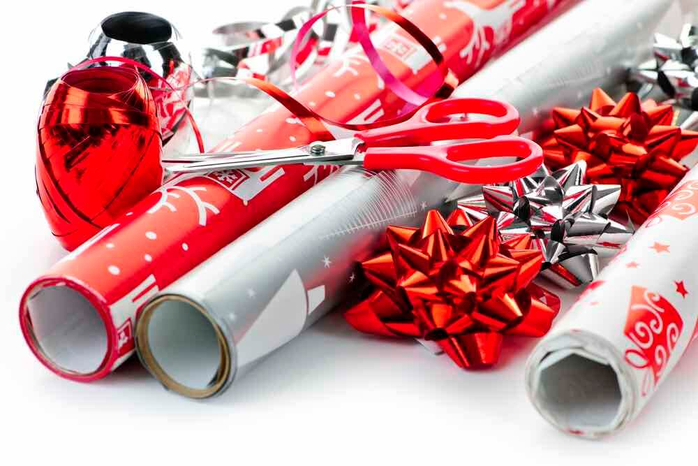 How to Store Christmas Ornaments So They Won't Break, tips featured by top Seattle lifestyle blogger, Marcie in Mommyland: Use leftover wrapping paper to protect your Christmas ornaments. Image of Rolls of Christmas wrapping paper with ribbons, bows and scissors