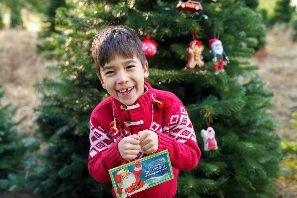 How to take your own DIY Christmas Family Portraits, tips featured by top Seattle lifestyle blogger, Marcie in Mommyland. There are tons of fun Christmas photo props to bring on your Christmas family portrait photo shoot. Image of a boy wearing battery powered Christmas lights while holding a little sign.