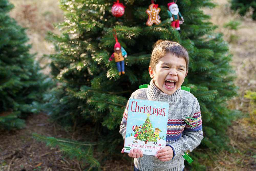 How to take your own DIY Christmas Family Portraits, tips featured by top Seattle lifestyle blogger, Marcie in Mommyland. Find out how to take Christmas familiy portraits at a Christmas tree farm. Image of a boy holding a Christmas book and laughing.