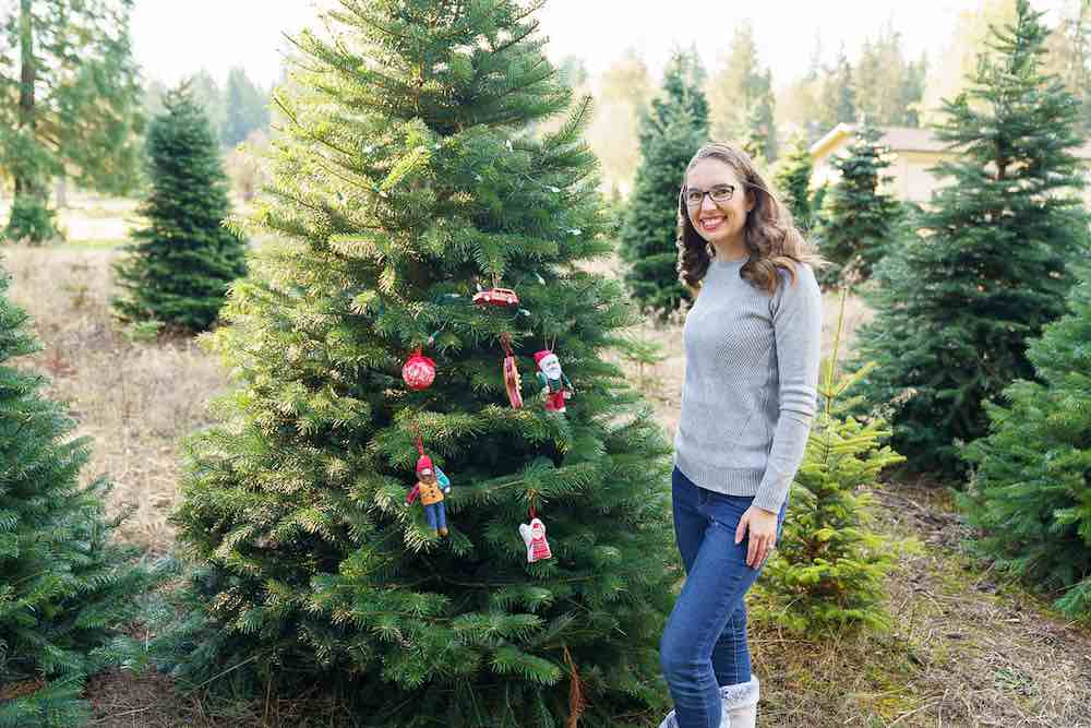 How to take your own DIY Christmas Family Portraits, tips featured by top Seattle lifestyle blogger, Marcie in Mommyland. Christmas tree farms are the ultimate spot for outdoor Christmas pictures. Image of a mom posing in front of a tree at a Christmas tree farm.