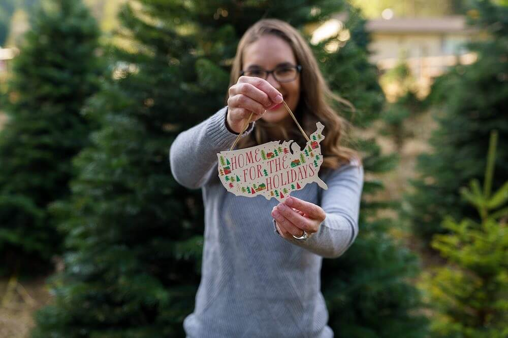 How to take your own DIY Christmas Family Portraits, tips featured by top Seattle lifestyle blogger, Marcie in Mommyland. Find out how to take family Christmas portraits yourself. Image of a woman holding a large ornament that says Home for the Holidays