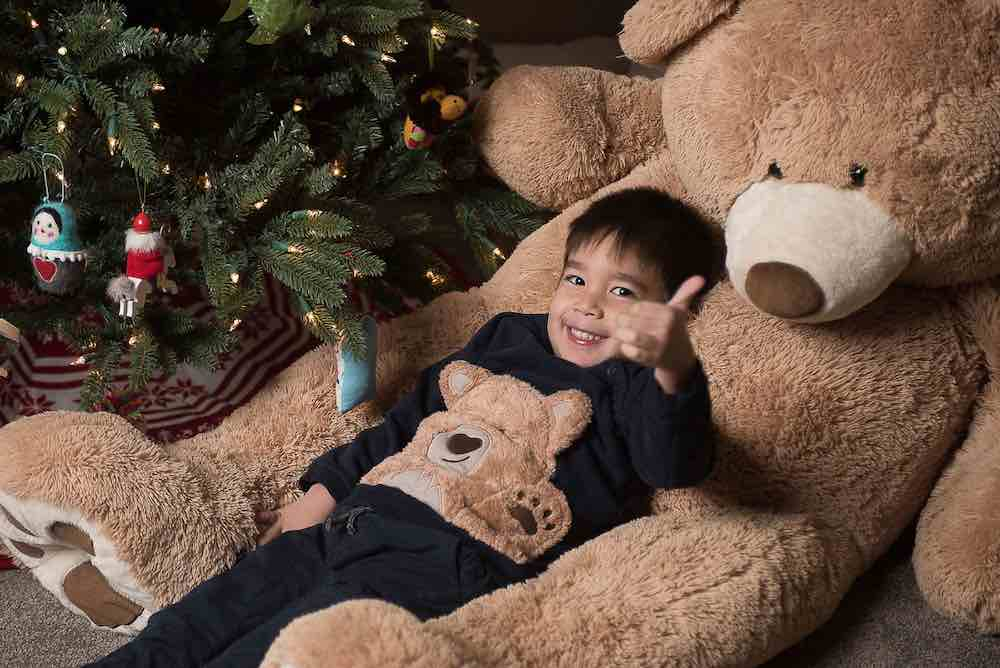 How to take your own DIY Christmas Family Portraits, tips featured by top Seattle lifestyle blogger, Marcie in Mommyland. Consider taking Christmas family portraits in front of your Christmas tree. Image of a boy lounging in a giant teddy bear in front of a Christmas tree.
