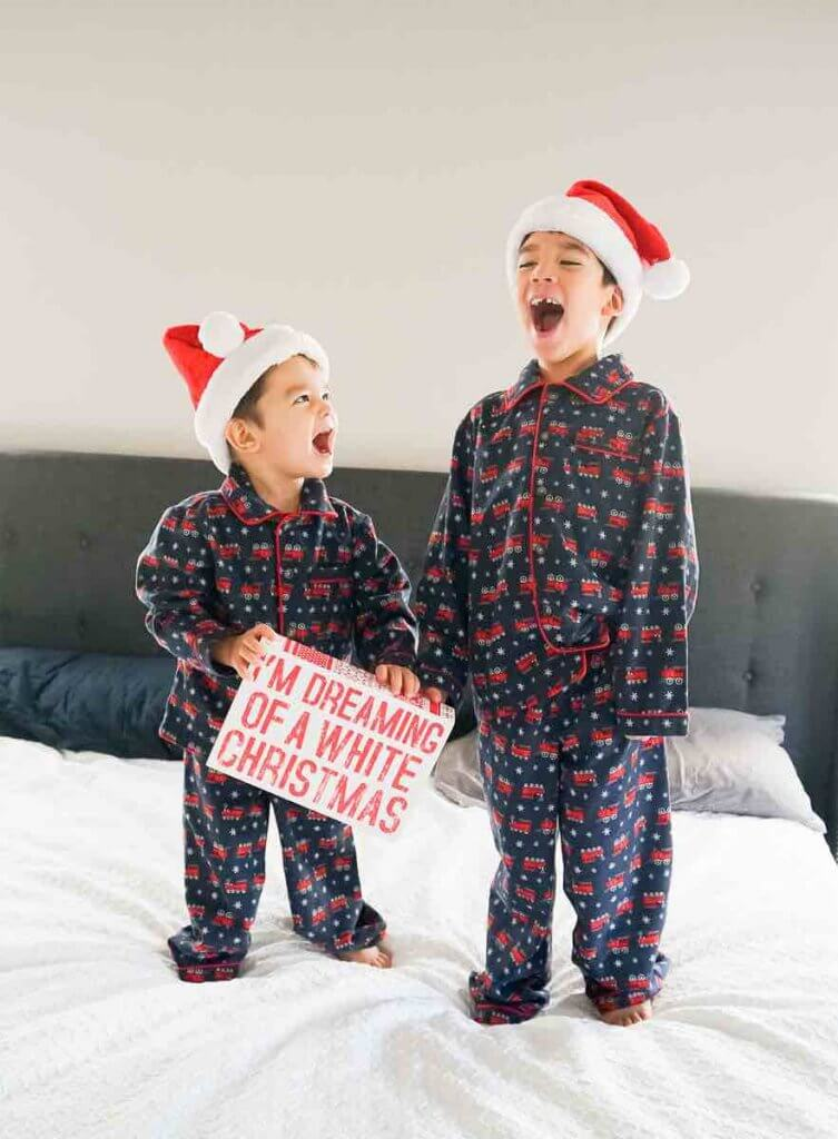 How to take your own DIY Christmas Family Portraits, tips featured by top Seattle lifestyle blogger, Marcie in Mommyland. Pajamas are popular Christmas picture outfit ideas.Image of two boys in Christmas jammies laughing on a bed.