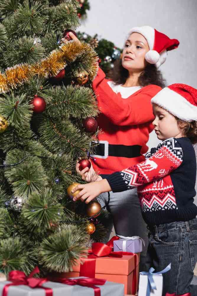 10 Best Secret Places to Hide Christmas Presents featured by top US lifestyle blogger, Marcie in Mommyland featured by top Seattle lifestyle blogger, Marcie in Mommyland: Find out how to decorate your Christmas tree with kids. Image of a mom and child decorating a Christmas tree
