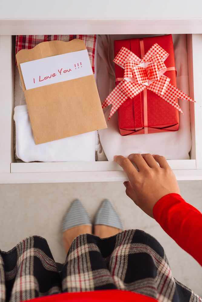 10 Best Secret Places to Hide Christmas Presents featured by top US lifestyle blogger, Marcie in Mommyland: Closet drawers are a great Christmas present hiding spot. Image of Woman hiding present and greeting card in the drawer, view from above