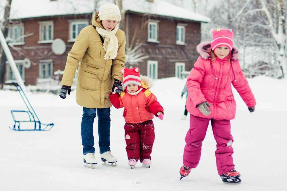 15 Free Festive Christmas Traditions That Don't Cost a Dime featured by top Seattle lifestyle blogger, Marcie in Mommyland: Add ice skating to your Christmas Bucket List. Image of Mother with her daughters skates on ice skating in the winter.
