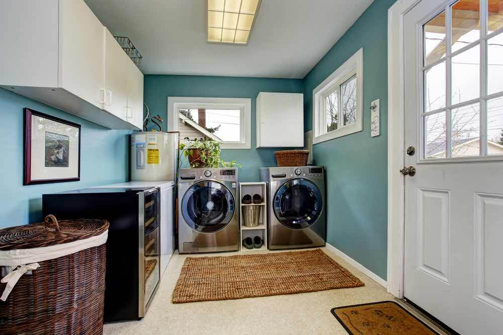 10 Best Secret Places to Hide Christmas Presents featured by top US lifestyle blogger, Marcie in Mommyland: You can hide Christmas presents in your laundry room. Image of Light blue laundry room with modern steel appliances and white cabinets