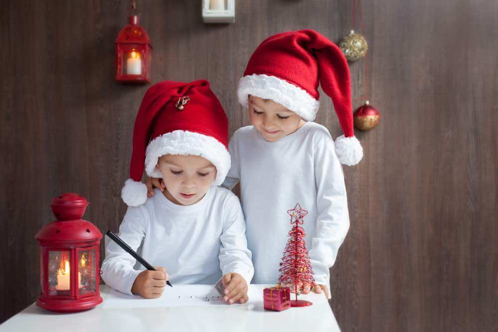 15 Free Festive Christmas Traditions That Don't Cost a Dime featured by top Seattle lifestyle blogger, Marcie in Mommyland: Writing a letter to Santa is an easy Christmas tradition for kids. Image of Two adorable boys, writing letter to Santa