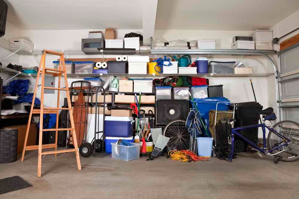 10 Best Secret Places to Hide Christmas Presents featured by top US lifestyle blogger, Marcie in Mommyland: There are so many places to hide Christmas presents in your garage. Image of Suburban garage mess. Boxes, tools and toys in disarray.