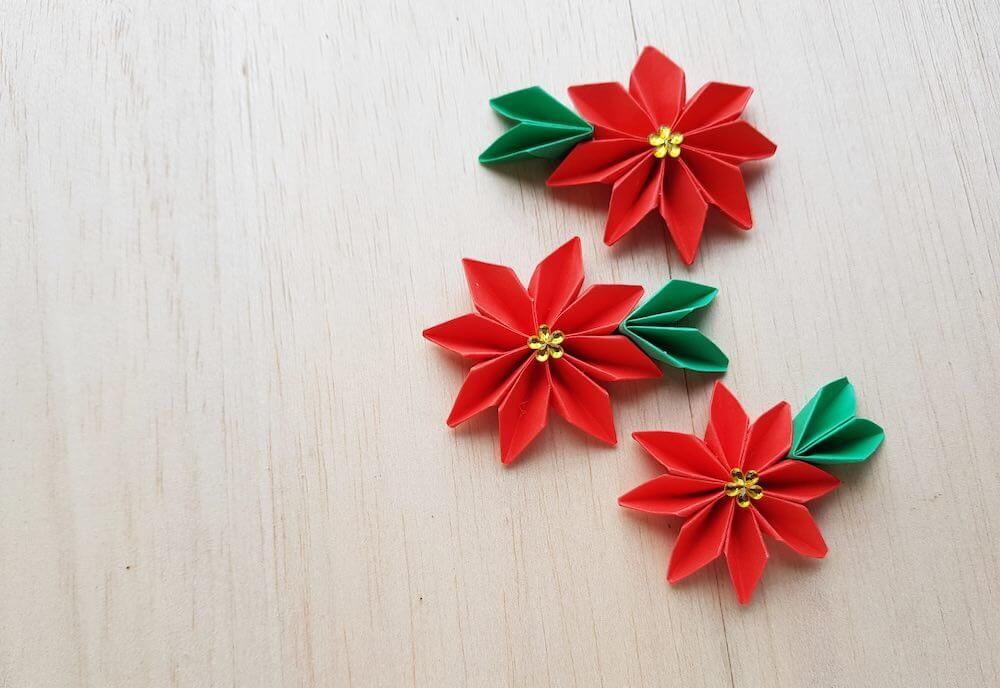 15 Free Festive Christmas Traditions That Don't Cost a Dime featured by top Seattle lifestyle blogger, Marcie in Mommyland: This origami poinsettia flower tutorial is easy to follow and so cute to make! Image of red origami poinsettia flowers