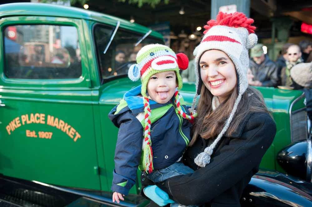 How to take your own DIY Christmas Family Portraits, tips featured by top Seattle lifestyle blogger, Marcie in Mommyland. Find out family Christmas picture outfit ideas. Image of a mom and son wearing sock money hats in front of a vintage green truck