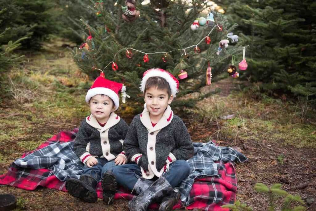How to take your own DIY Christmas Family Portraits, tips featured by top Seattle lifestyle blogger, Marcie in Mommyland. One of my favorite Christmas photography props is using a plaid blanket. Image of two boys sitting on a plaid blanket at a Christmas tree farm.