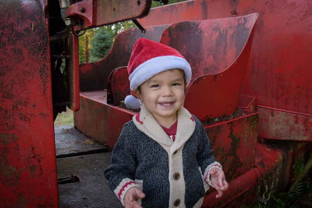 How to take your own DIY Christmas Family Portraits, tips featured by top Seattle lifestyle blogger, Marcie in Mommyland. Wearing a Santa hat is always a fun addition to any holiday photo outfit ideas. Image of a toddler wearing a Santa hat.