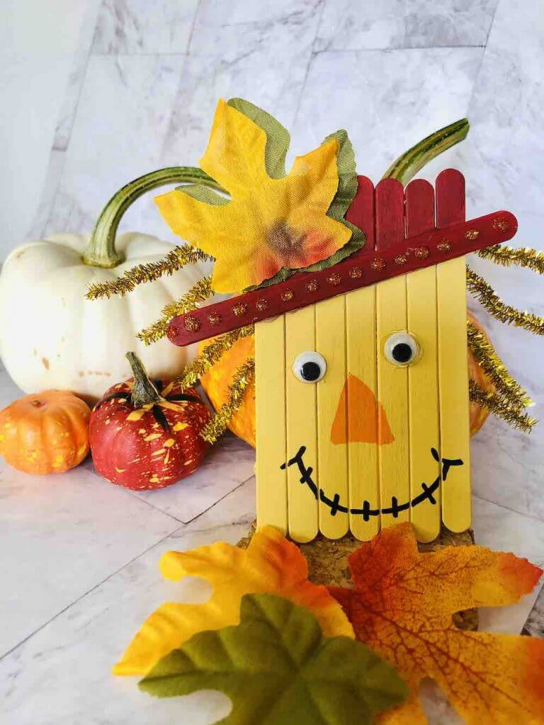 Final image of popsicle stick scarecrow craft in front of pumpkins
