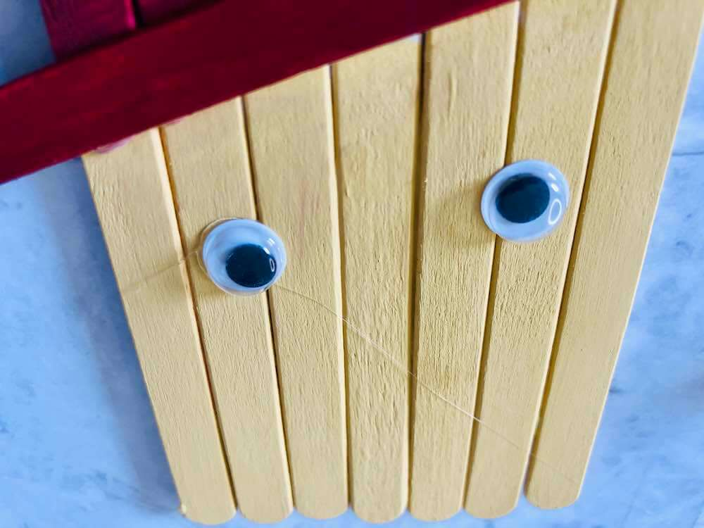 How to make a popsicle stick scarecrow craft step 5. Image of googly eyes on the scarecrow