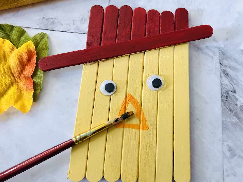 How to make a popsicle stick scarecrow craft step 6. Image of someone painting an orange nose on the scarecrow