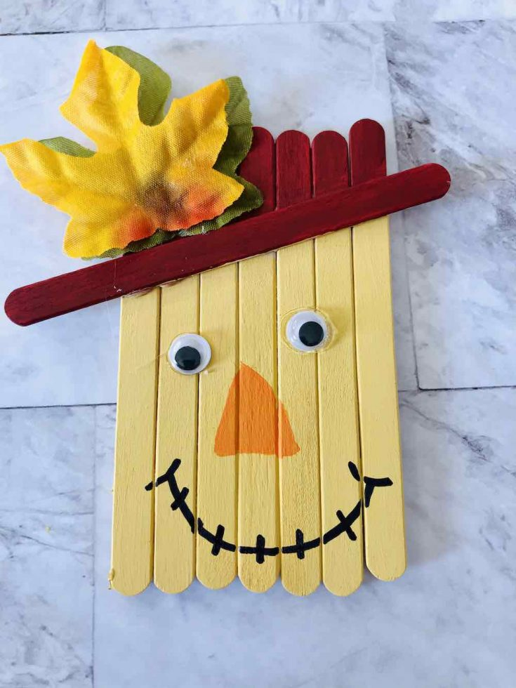 How to make a popsicle stick scarecrow craft. Image of the mouth drawn on