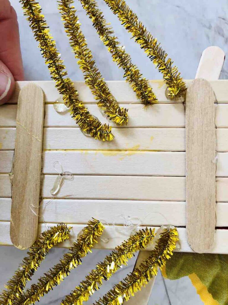 How to make a popsicle stick scarecrow. Image of gold pipe cleaners glued on back for hair