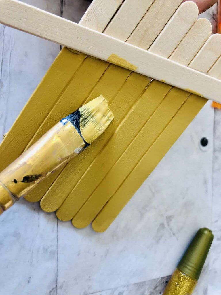 How to make a popsicle stick scarecrow craft step 4. Image of someone painting popsicle sticks yellow