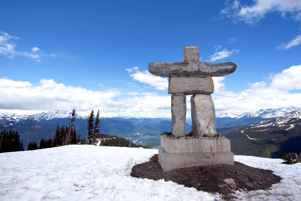 Best Winter Weekend Getaways from Seattle featured by top Seattle travel blogger, Marcie in Mommyland: Image of Inukshuk at the top of Whistler Peak in British Columbia, Canada, with snow, blue sky, white clouds and mountains in the distance
