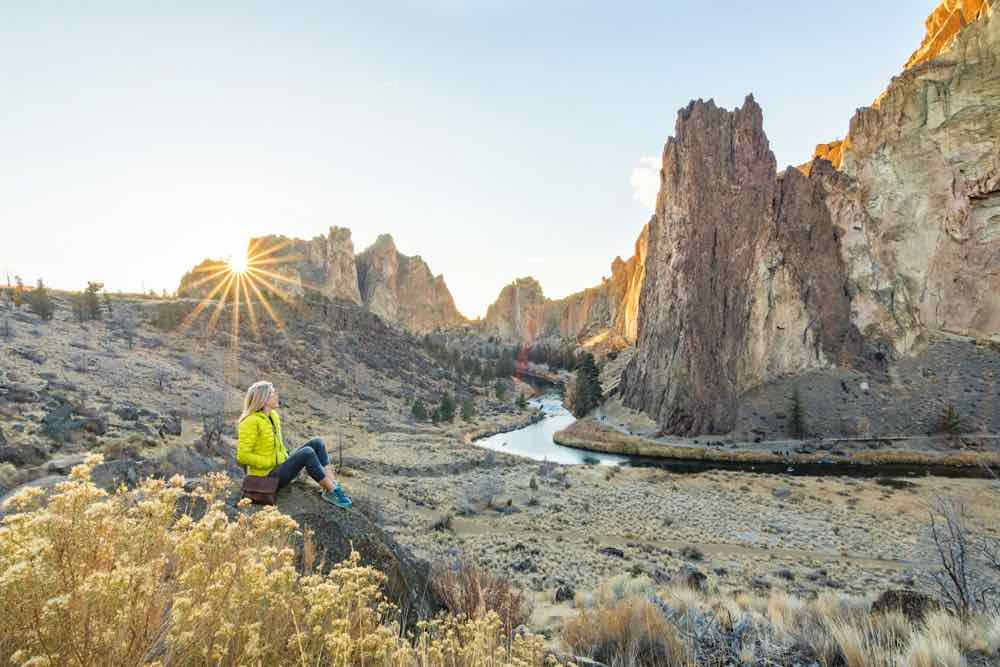 Best Winter Weekend Getaways from Seattle featured by top Seattle travel blogger, Marcie in Mommyland: Image of a woman sitting on a rock at Smith Rock State Park in Bend, Oregon